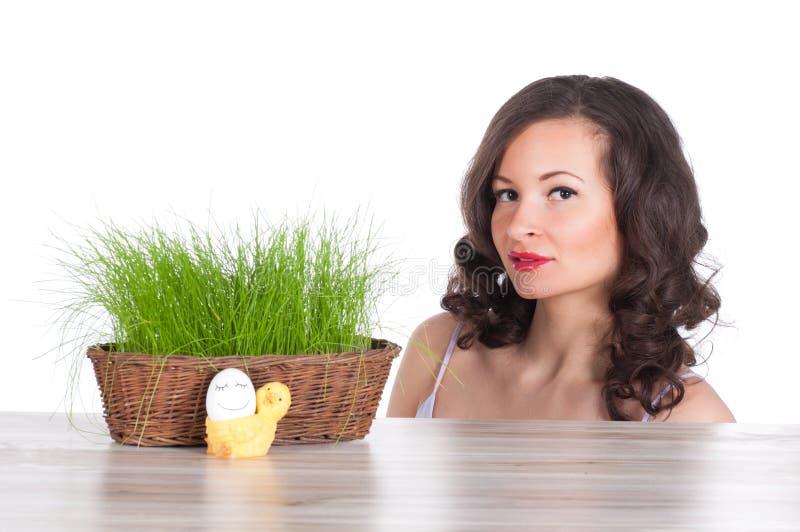 Красивая женщина с корзиной пасхи с зеленой травой, цыпленком и усмехаясь яичком стоковое фото rf