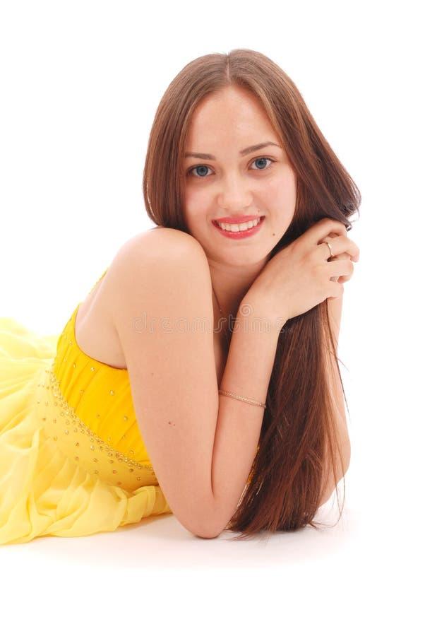 Красивая женщина с коричневыми волосами в элегантном желтом платье стоковое фото rf