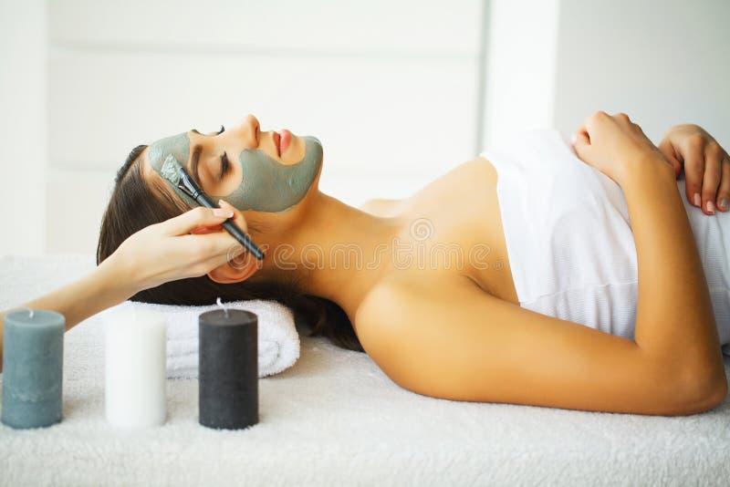 Красивая женщина с косметической маской на стороне Девушка получает обработку стоковое фото