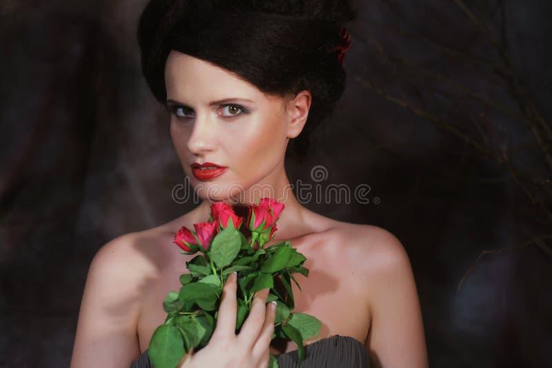 Красивая женщина с красными розами стоковые изображения rf