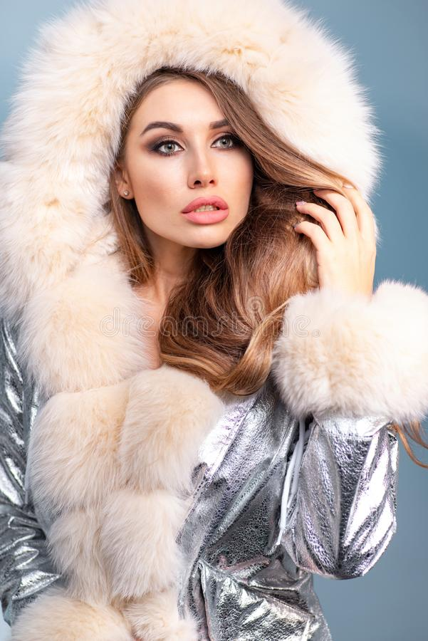Красивая женщина с макияжем в тёплом сияющем серебряном пальто с мехом, позирующим на фоне синей студии стоковые фото
