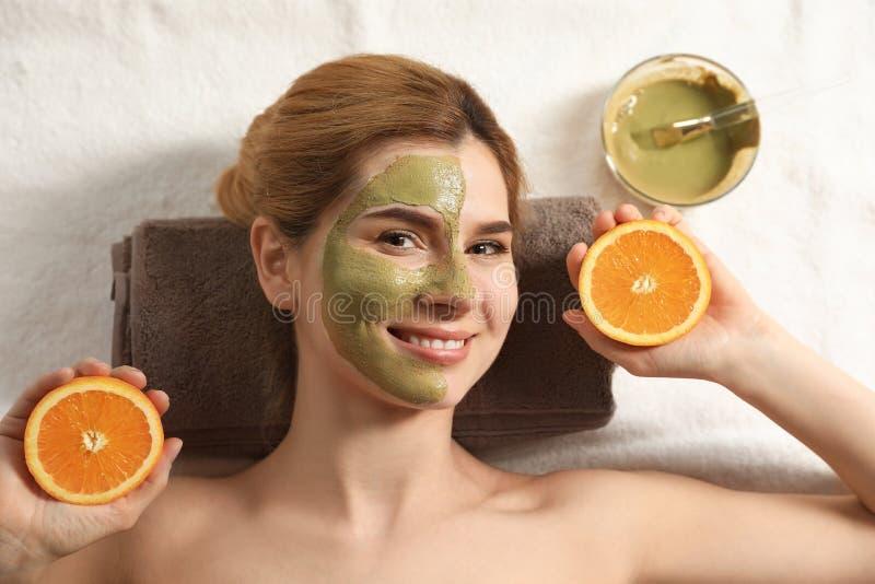 Красивая женщина с маской на стороне и отрезать оранжевый ослаблять стоковое фото