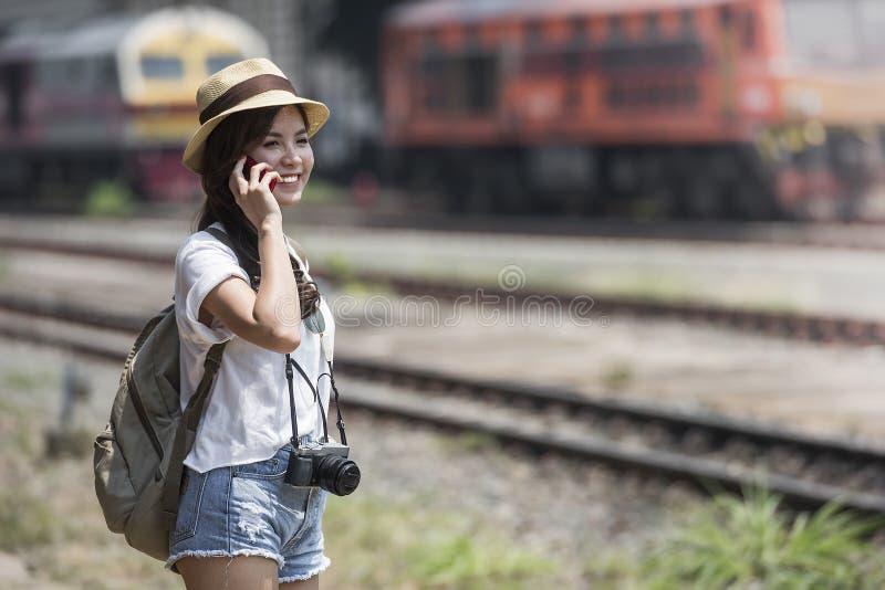 Красивая женщина с положением рюкзака и smartphone использования стоковые изображения