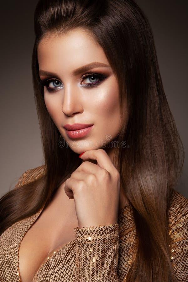 Красивая женщина с профессионалом составляет Платье золота стоковые изображения