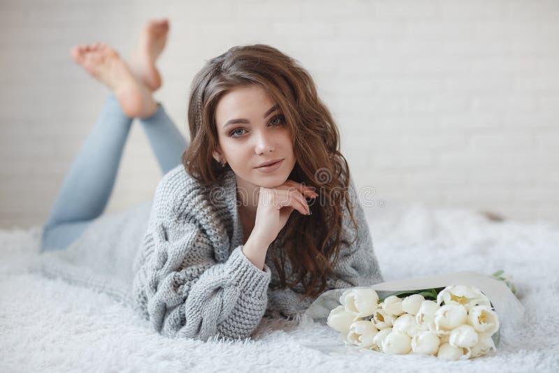 Красивая женщина с светлыми волосами в сером цвете связала свитер в яркой спальне на серой предпосылке стоковые изображения rf