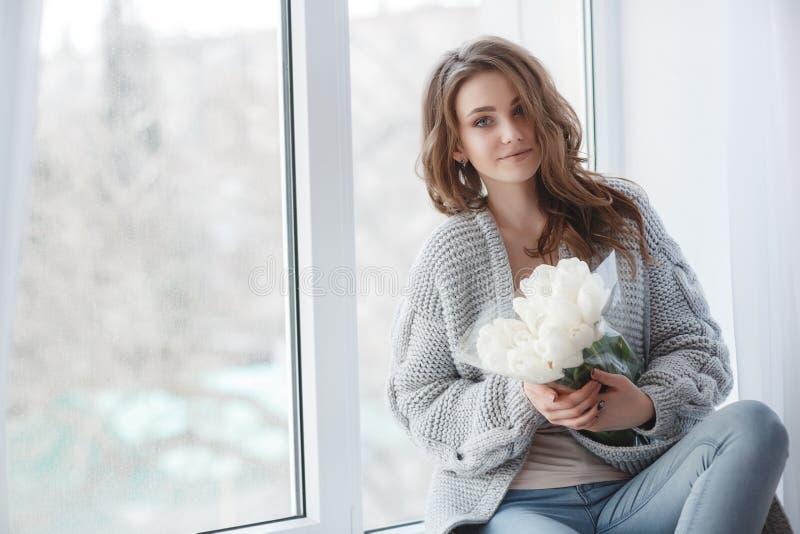 Красивая женщина с светлыми волосами в сером цвете связала свитер в яркой спальне на серой предпосылке стоковое изображение