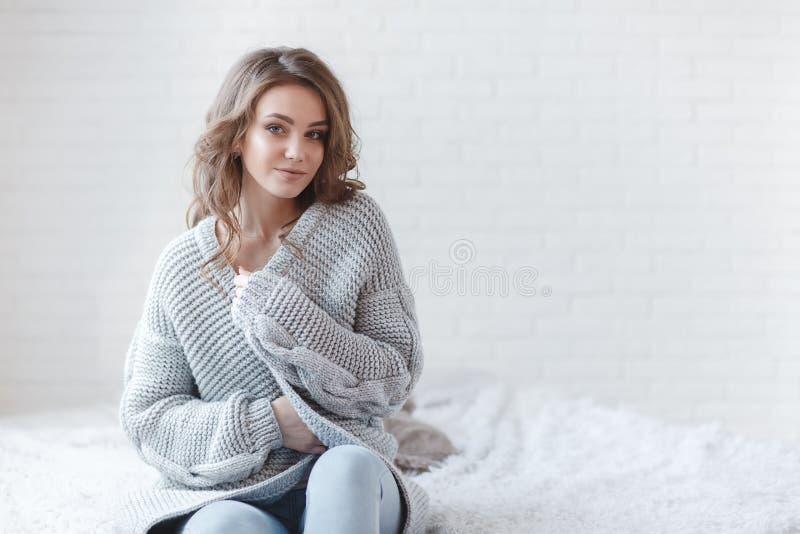 Красивая женщина с светлыми волосами в сером цвете связала свитер в яркой спальне на серой предпосылке стоковая фотография
