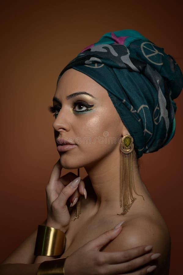 Красивая женщина с тюрбаном Молодая привлекательная женщина с тюрбаном и золотыми аксессуарами Женщина красоты модная стоковое фото rf