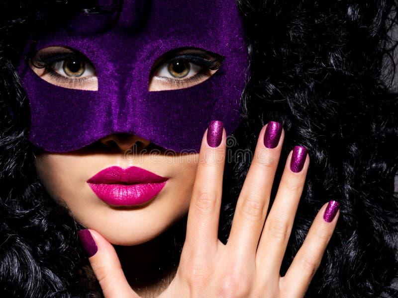 Красивая женщина с фиолетовой маской театра на стороне и фиолетовом na стоковое фото rf
