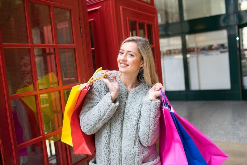 Красивая женщина с хозяйственными сумками в торговой улице, Лондоне стоковое изображение rf
