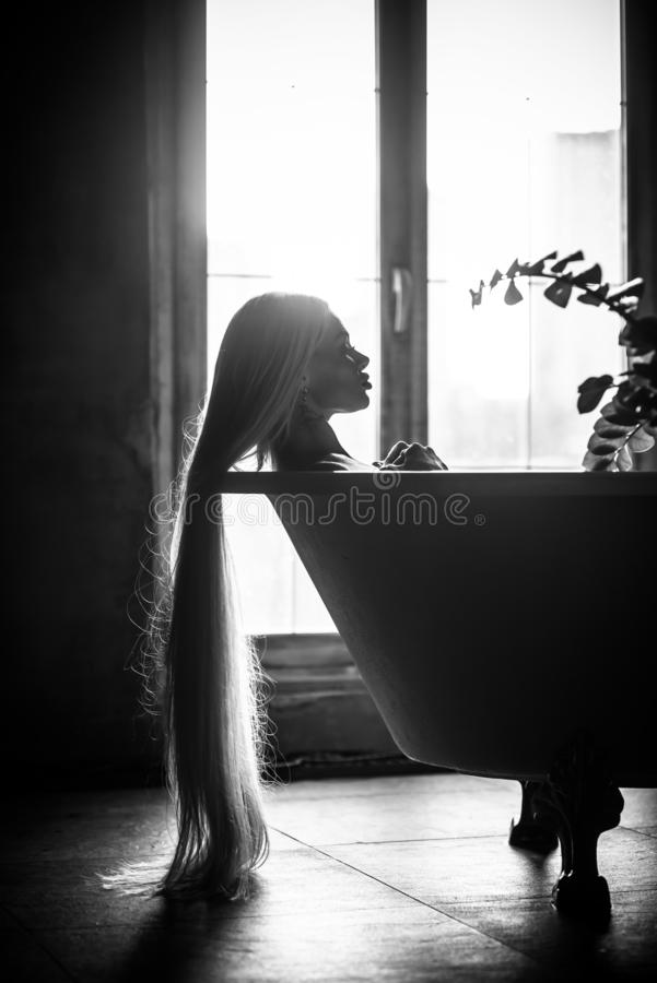 Красивая женщина с шикарными длинными светлыми волосами ослабляет в ванне Силуэт женщины в профиле лежа в bathroom стоковое изображение rf