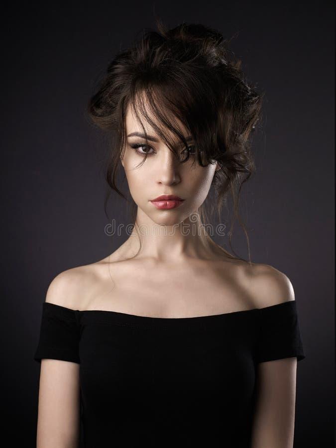 Красивая женщина с элегантным стилем причёсок на черной предпосылке стоковые фото