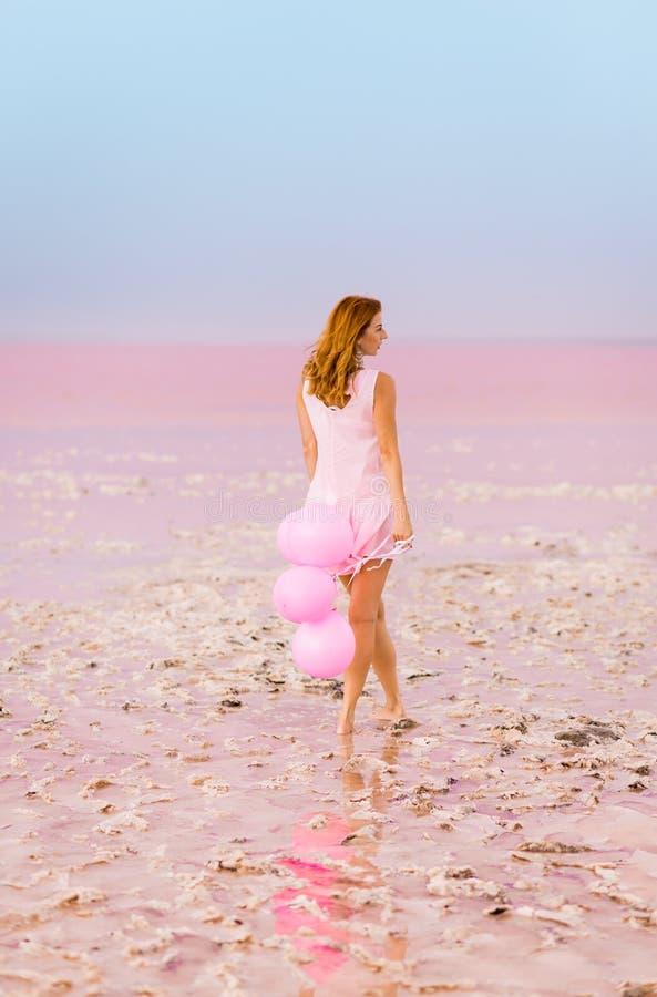 Красивая женщина с baloons на розовом озере соли стоковое фото rf