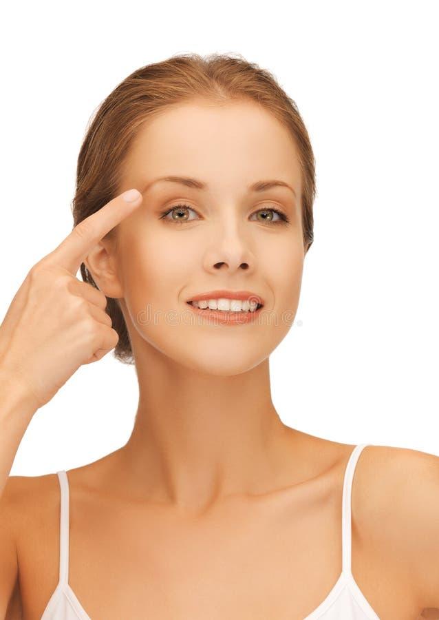 Красивая женщина указывая к брови стоковое фото rf