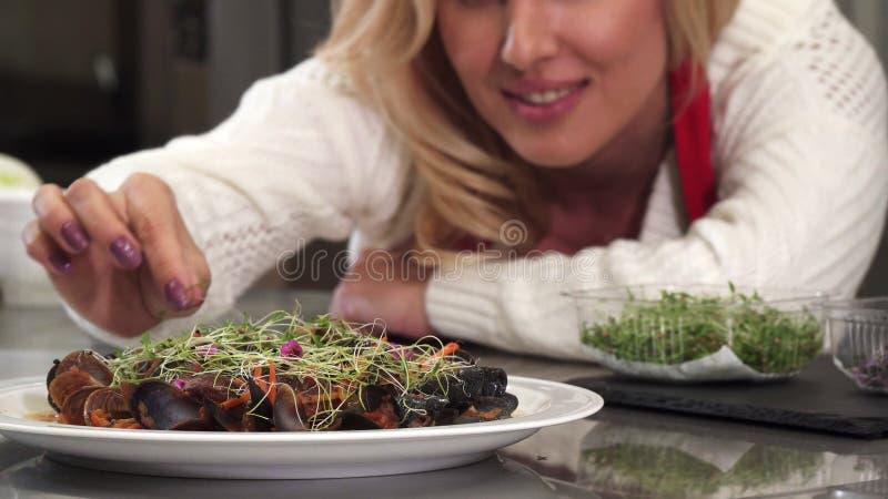 Красивая женщина украшая блюдо мидий на плите подготавливая еду дома стоковые изображения rf