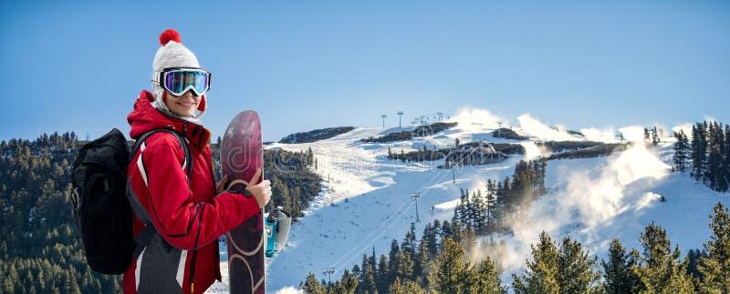 Красивая женщина усмехаясь и держа сноуборд стоковая фотография rf