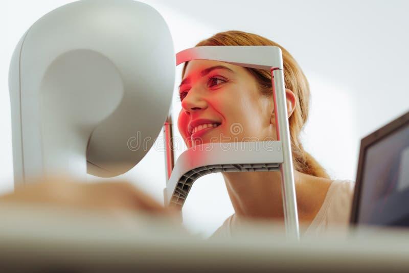Красивая женщина усмехаясь пока имеющ рассмотрение глаза стоковое фото rf