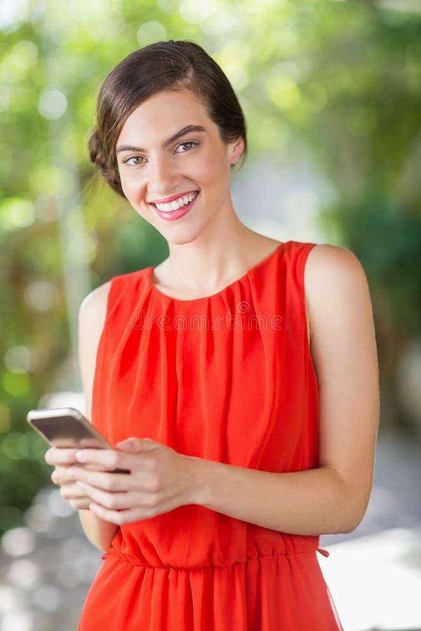 Красивая женщина усмехаясь пока использующ мобильный телефон стоковые изображения rf
