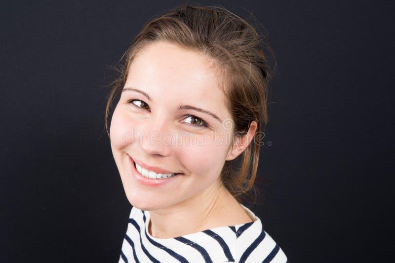 Красивая женщина усмехаясь против предпосылки стоковая фотография