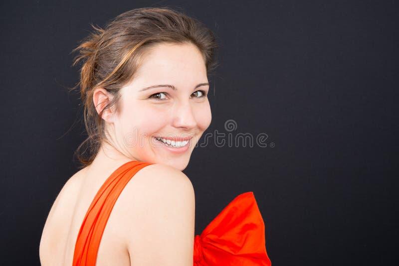 Красивая женщина усмехаясь против предпосылки стоковые фото