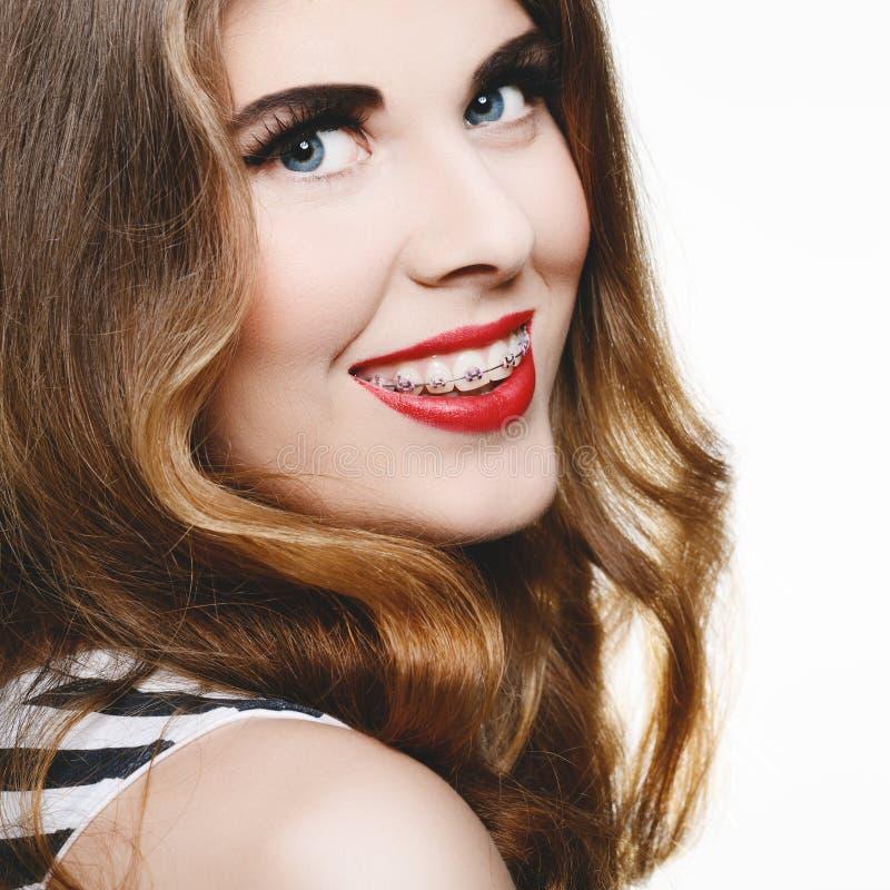 Красивая женщина усмехаясь с расчалками стоковое изображение