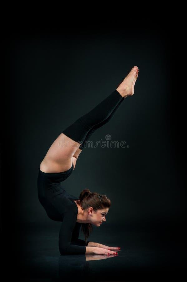 Красивая женщина фитнеса делая протягивающ тренировку на черном backg стоковая фотография