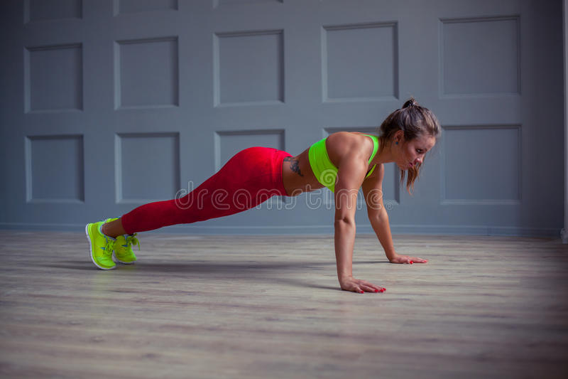 Красивая женщина фитнеса делает нажим-поднимает в спортзале, стоковая фотография