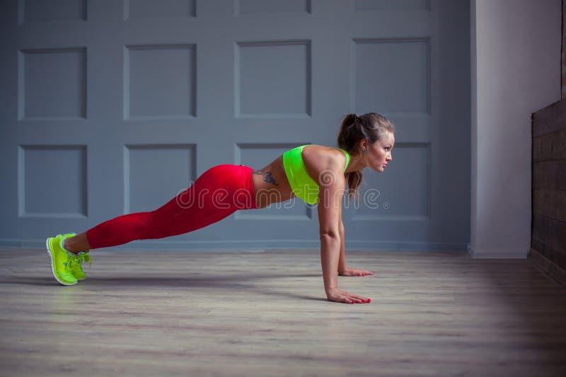 Красивая женщина фитнеса делает нажим-поднимает в спортзале, стоковое изображение rf