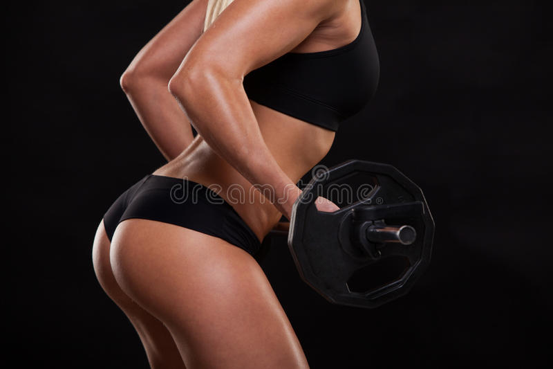 Красивая женщина фитнеса поднимает штангу Sporty девушка показывая ее вышколенное тело Изолировано на темной предпосылке стоковое изображение rf