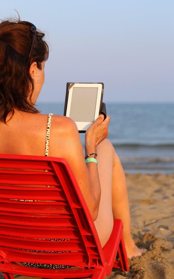 Красивая женщина читает ebook на пляже стоковая фотография