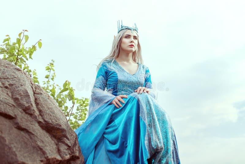 Красивая женщина эльфа сидит на горе стоковое изображение
