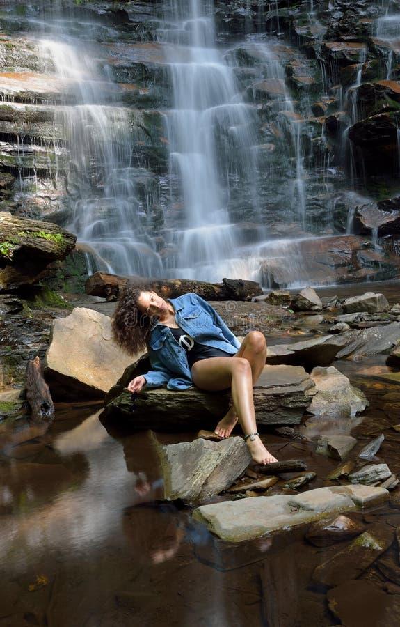 Красивая женщина outdoors - рядом с водопадом стоковое фото