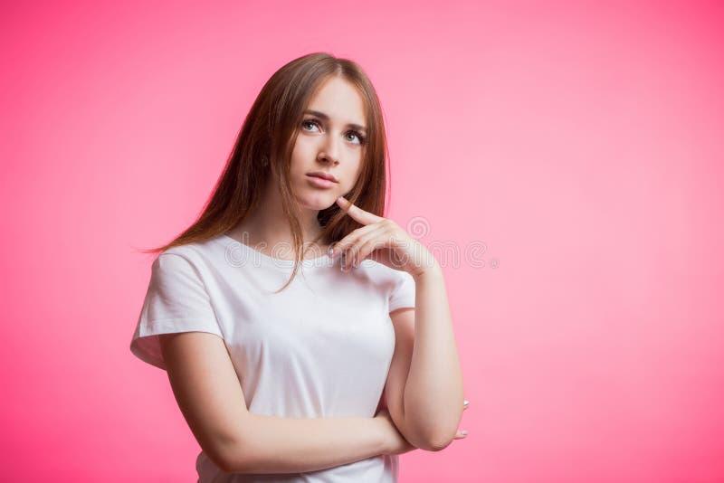 Красивая женщина redhead в белой рубашке смотрит вверх заботливо на розовой предпосылке с космосом экземпляра стоковые фото