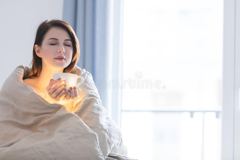 Красивая женщина rednead с чашкой кофе или капучино в кровати стоковое фото rf