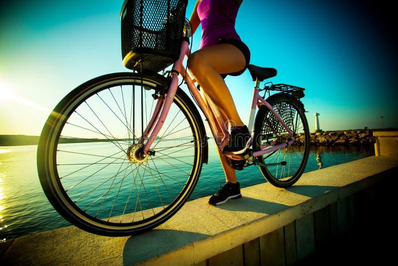 Красивая женщина streight с велосипедом на заходе солнца стоковые фотографии rf