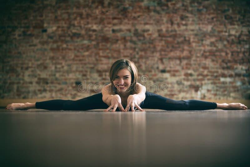 Красивая женщина yogini практикует позицию прямого угла Samakonasana asana йоги в студии йоги на предпосылке кирпичной стены стоковая фотография rf