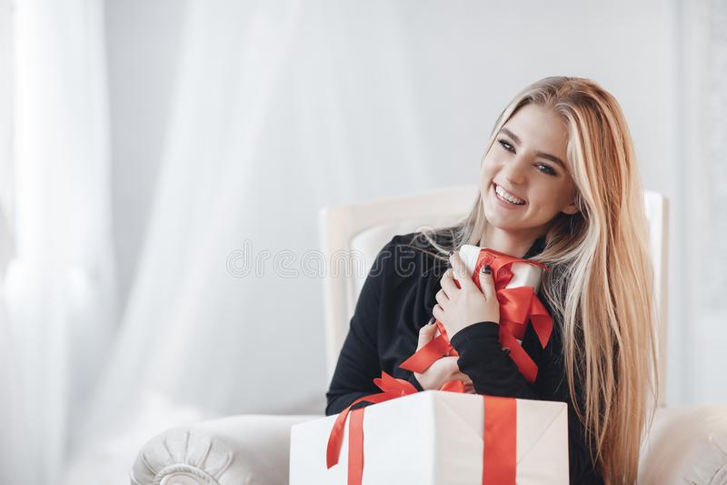 Красивая жизнерадостная женщина с подарками на белой предпосылке стоковая фотография
