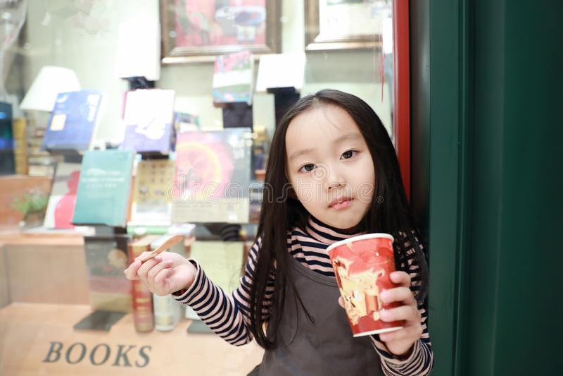 Красивая жизнерадостная маленькая девочка ест мороженое стоковое изображение rf
