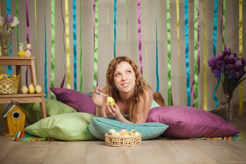 Красивая жизнерадостная женщина в красочном интерьере пасхи стоковое фото rf