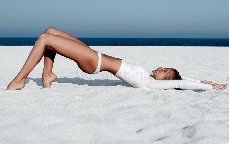 Красивая загоренная женщина в белом купальнике на пляже стоковое фото rf