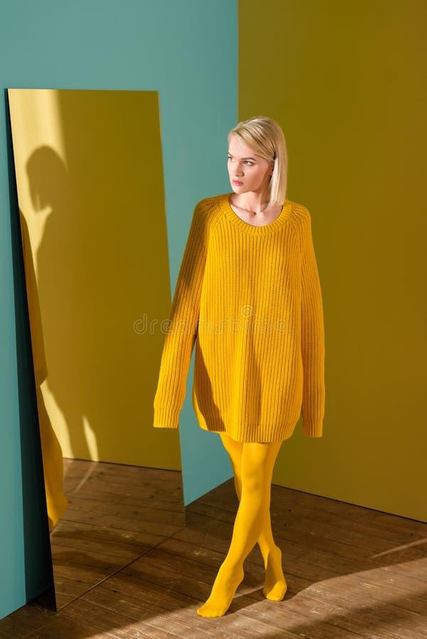 красивая задумчивая белокурая женщина в желтом положении свитера и колготков стоковые фото