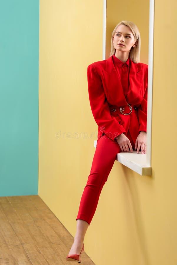 красивая задумчивая женщина в стильный красный сидеть костюма стоковые изображения