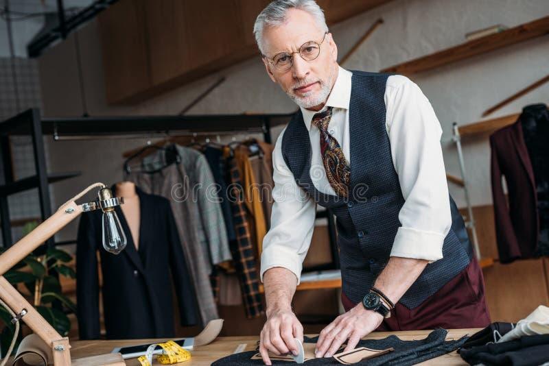 красивая зрелая картина ткани маркировки портноя с мелом на шить мастерской и смотреть стоковое фото rf
