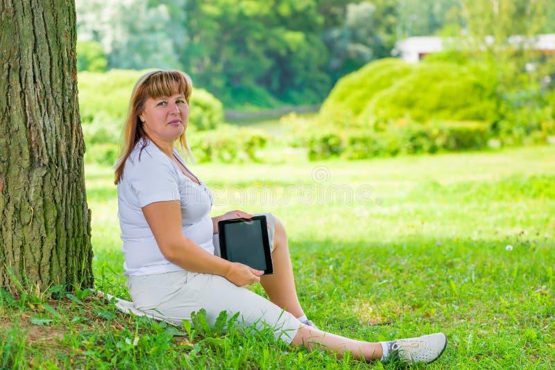 Красивая зрелая женщина около дерева в парке стоковые изображения rf