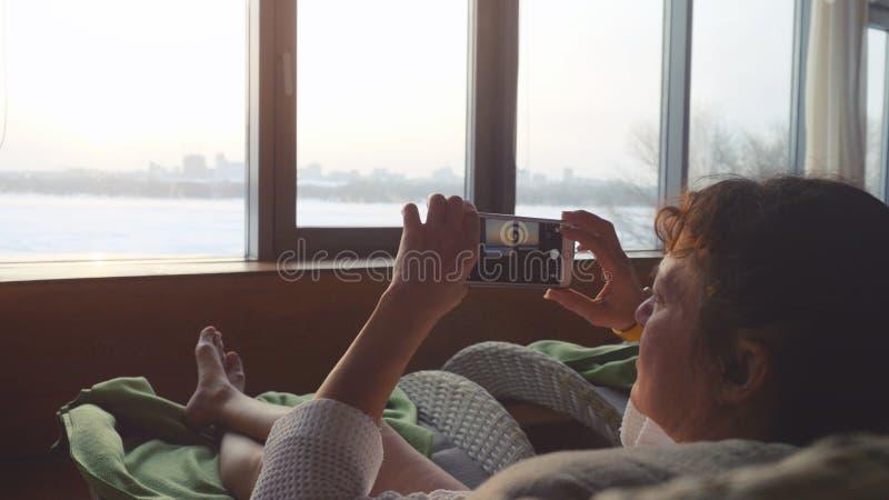 Красивая зрелая женщина ослабляя в курорте и фотографируя от ее умного телефона лежа на софе и заходе солнца взглядов от стоковое изображение rf