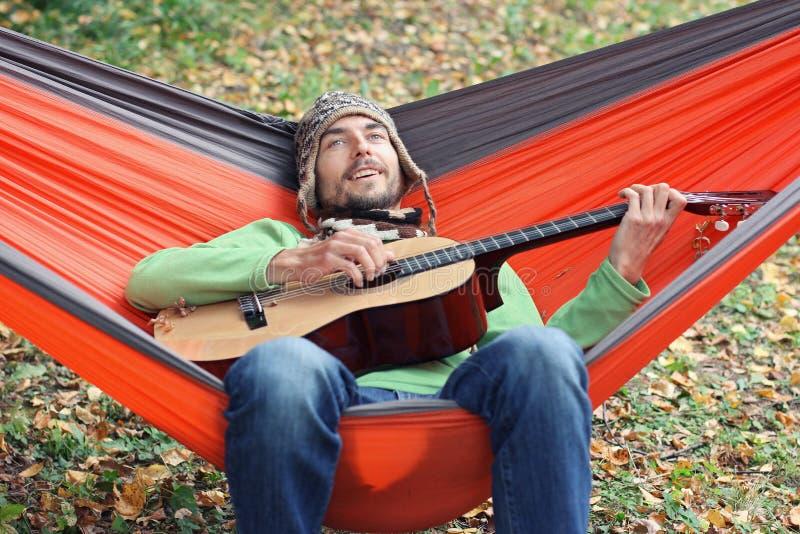 Красивая игра hiker человека на гитаре пока сидящ в гамаке после отключения в концепции образа жизни леса осени располагаясь лаге стоковые изображения rf