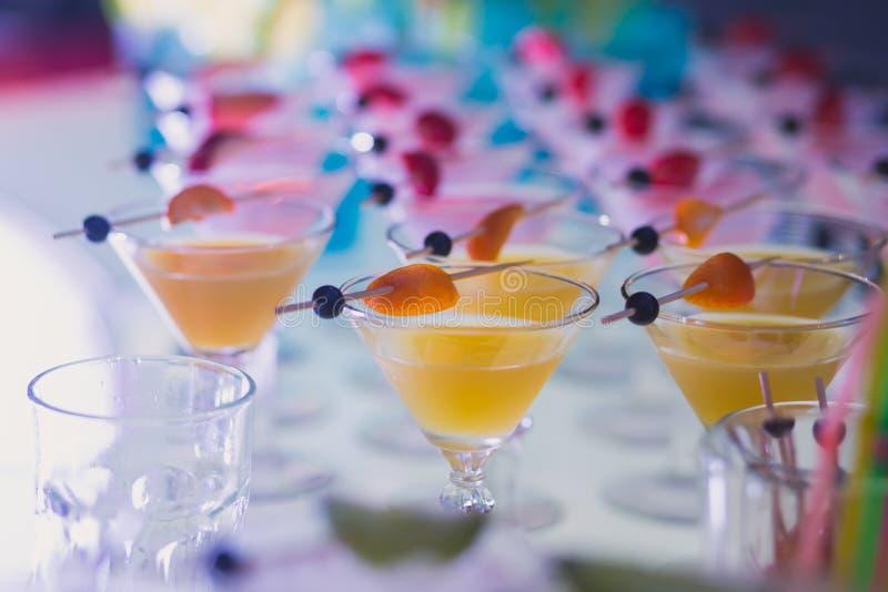 Красивая линия различных покрашенных коктеилей спирта с дымом на рождественской вечеринке, текила, Мартини, водочке, и других на  стоковое фото