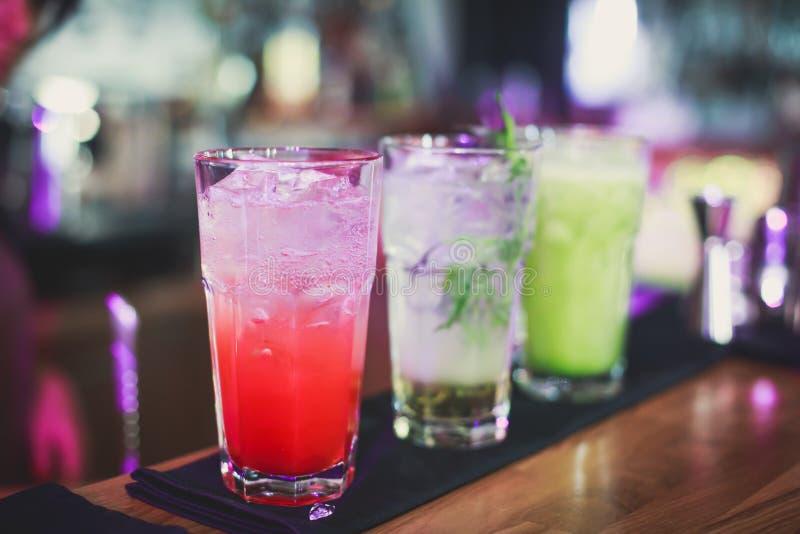 Красивая линия различных покрашенных коктеилей спирта с дымом на рождественской вечеринке, текила, Мартини, водочке, и других на  стоковое фото rf