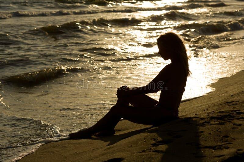 Красивая, длинная с волосами тонкая молодая женщина на пляже, заход солнца стоковое изображение