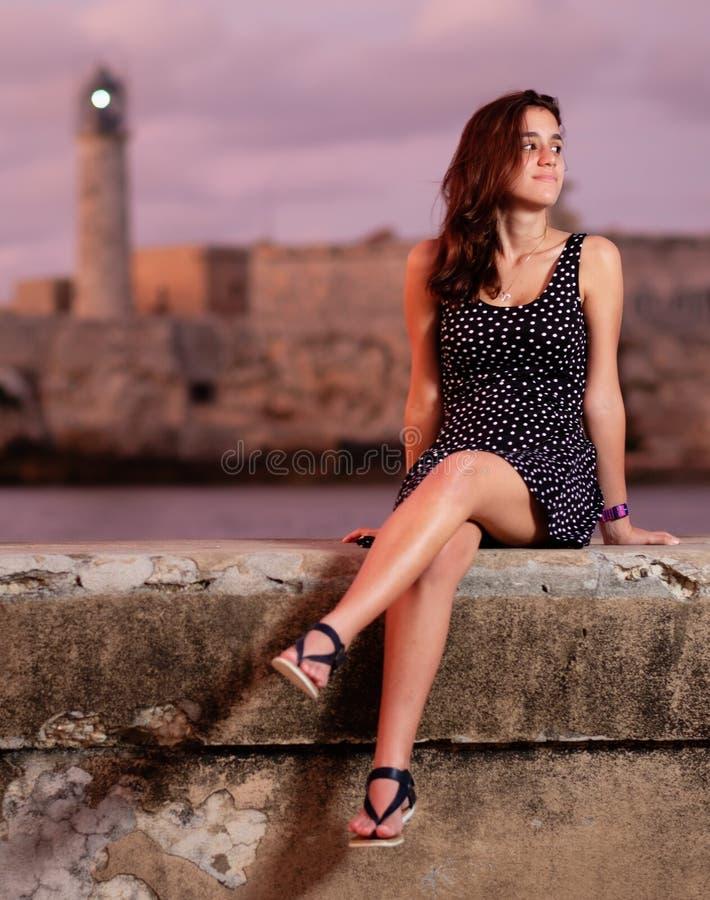 Красивая испанская девушка сидя на морской дамбе Malecon на заходе солнца в Гаване стоковое изображение